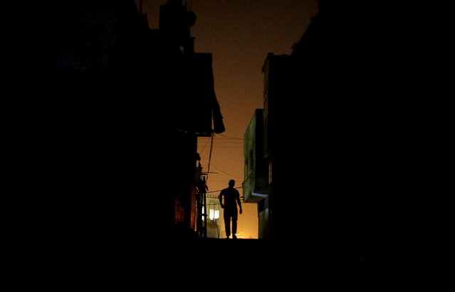 A Palestinian man walks at Shatti (beach) refugee camp during power cut, in Gaza City July 23, 2015. Palestinian Energy officials said residents of Gaza, home to 1.8 million people, have been experiencing up to 18 hours of electricity outage a day for three days due to fuel and power shortages. (Photo by Mohammed Salem/Reuters)