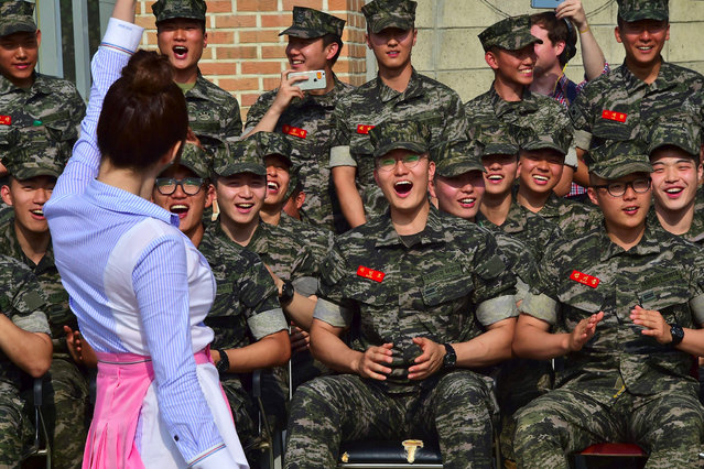 """South Korean marines react as they watch a performance of K-pop girl group Laboum at a military base in Gimpo near the Demilitarized zone dividing the two Koreas on June 10, 2016. South Korean girl group Laboum performing a month-long event as part of """"Thank You! Soldiers"""" campaign organized by the Defence Ministry to help boost troop morale in the country's frontline troops through performances, autograph sessions and other events. (Photo by Jung Yeon-Je/AFP Photo)"""