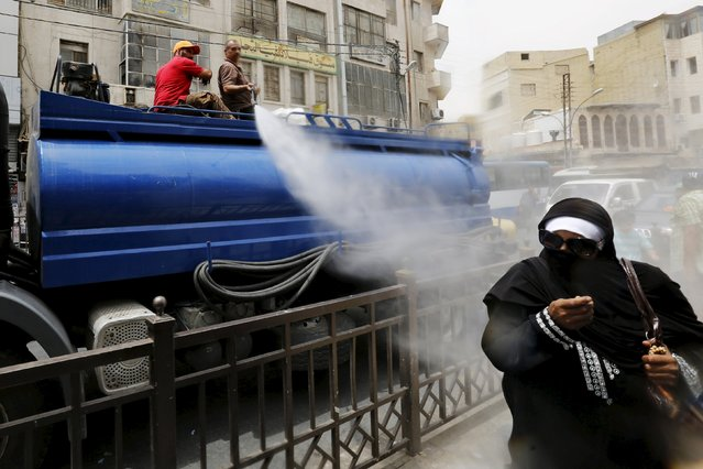 Greater Amman Municipality personnel spray people with a water sprinkler in order to cool them down as part of measures to ease the effect of a heatwave, in Amman, Jordan, August 3, 2015. (Photo by Muhammad Hamed/Reuters)