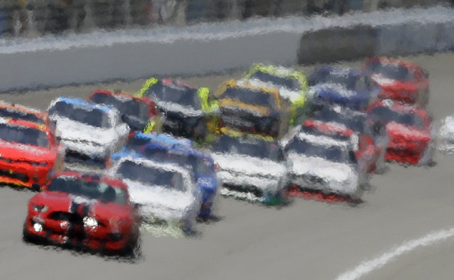 Heat waves distort this image of drivers following the pace car during the NASCAR Xfinity series auto race at Michigan International Speedway, Saturday, June 11, 2016 in Brooklyn, Mich. (Photo by Carlos Osorio/AP Photo)