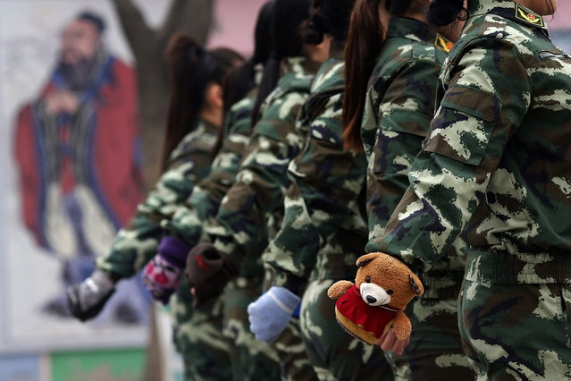 Female students wearing gloves take part in a military-style close-order drill class at the Qide Education Center in Beijing February 19, 2014. The Qide Education Center is a military-style boot camp which offers treatment for internet addiction. As growing numbers of young people in China immerse themselves in the cyber world, spending hours playing games online, worried parents are increasingly turning to boot camps to crush addiction. (Photo by Kim Kyung-Hoon/Reuters)
