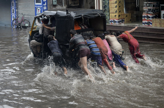 Indian children help to push an auto rickshaw along a flooded street after heavy rain in Jalandhar on June 29, 2017, as the monsoon season begins. (Photo by Shammi Mehra/AFP Photo)