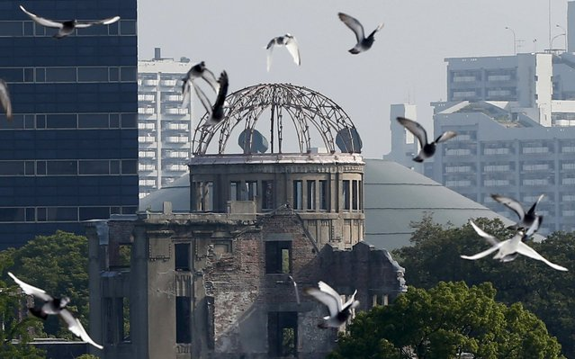 Doves fly over Peace Memorial Park with Atomic Bomb Dome in the background, at a ceremony in Hiroshima, western Japan, August 6, 2015, on the 70th anniversary of the atomic bombing of the city. (Photo by Toru Hanai/Reuters)