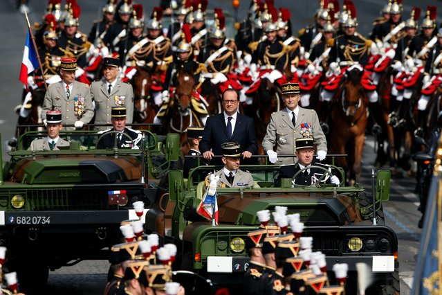 France's President Francois Hollande (L) and French Army Chief of Staff, General Pierre de Villiers ride in a command car during the traditional Bastille Day parade on the Champs Elysees in Paris July 14, 2014. (Photo by Benoit Tessier/Reuters)