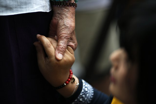 """Former South Korean """"comfort woman"""" Kim Bok-dong (L) holds hands with an activist while she makes a speech during the weekly Wednesday protest in front of the Japanese embassy demanding for an apology and compensation from the Japanese government in Seoul, South Korea, July 22, 2015. (Photo by Kim Kyung-Hoon/Reuters)"""
