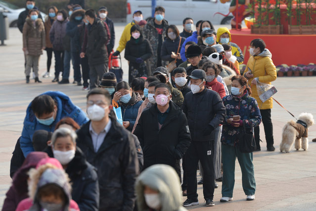 People line up outside a drugstore to buy medical masks in Nanjing, Jiangsu province, China, 29 January 2020. According to media reports, coronavirus, which in severe cases causes pneumonia, killed 132 people and infected nearly 6,000, mainly in China. Governments around the world are taking preventative measures to health the spread of the virus. (Photo by Fang Dongxu/EPA/EFE)