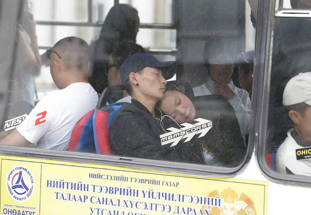 A couple takes a nap in a bus in Ulaanbaatar, Mongolia, June 28, 2016. (Photo by Jason Lee/Reuters)