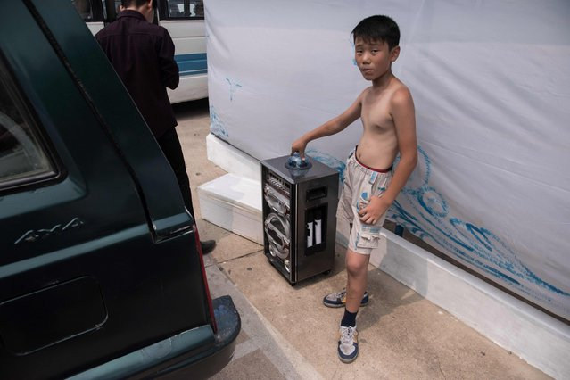 A photo taken on July 22, 2017 shows a boy standing with a karaoke machine at the West Sea Barrage beach outside the coastal city of Nampo, southwest of Pyongyang. The West Sea Barrage beach features as a stopping point for foreign tourists, and is a destination for North Korean work groups from the neighbouring area. The beach lies at the end of an eight- kilometre- long barrage that separates the sea from the Taedong River, which runs through Pyongyang. (Photo by Ed Jones/AFP Photo)