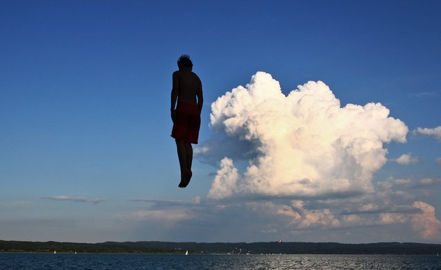 A photo made available 24 July 2014 of a young man who appears to fly in the air while being backdropped by a dramatic constallation of clouds as he jumps from a tower at a public bathing beach into the Lake Ammersee, in Utting, Bavaria state, Germany, 23 July 2014. (Photo by Karl-Josef Hildenbrand/EPA)