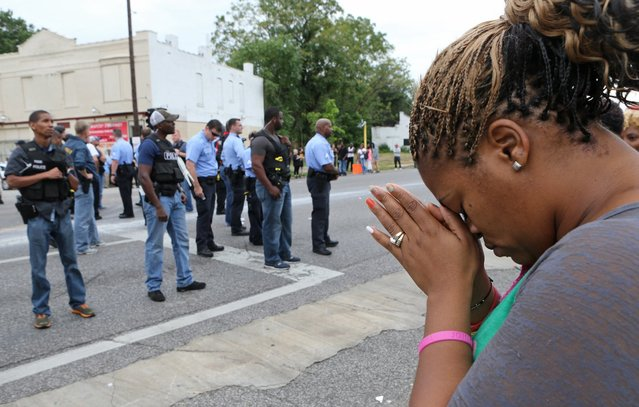 Rhonda Tunstall, 40, prays for peace in the middle of the street as police move in to disperse the large crowd gathered at Page and Walton, Wednesday, August 19, 2015 in St. Louis. An armed man fleeing from officers serving a search warrant at a home in a crime-troubled section of north St. Louis was shot and killed Wednesday by police after he pointed a gun at them, the police chief said. (Photo by David Carson/St. Louis Post-ispatch via AP Photo)