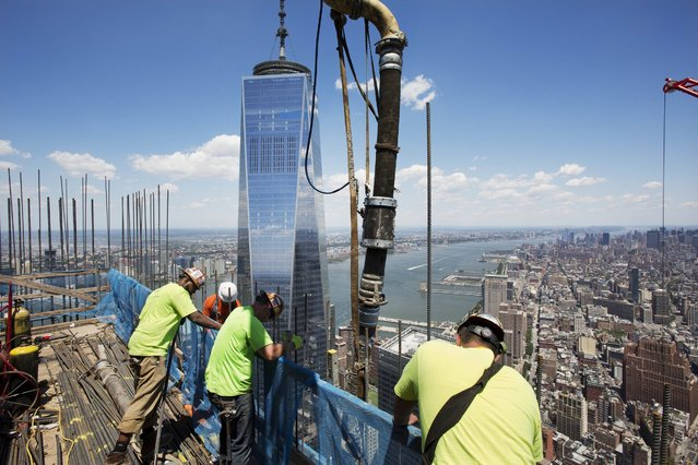 In this Wednesday, June 22, 2016 photo, workers guide a boom pouring concrete on top of 3 World Trade Center in New York. Behind them is One World Trade Center. (Photo by Mark Lennihan/AP Photo)