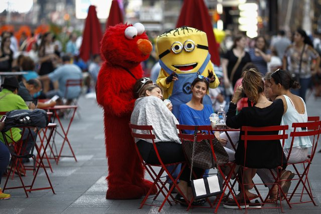 Jorge, an immigrant from Mexico, poses with women while dressed as the Sesame Street character Elmo in Times Square, New York July 30, 2014. (Photo by Eduardo Munoz/Reuters)