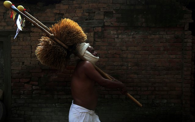 A Nepalese Hindu devotee carries water-soaked hay as part of rituals during Madhav Narayan festival in Thecho, Lalitpur, Nepal, Thursday, February 6, 2020. During this month-long festival, devotees recite Holy Scriptures dedicated to Hindu goddess Swasthani and Hindu God Lord Shiva. Unmarried women pray to get a good husband while those married pray for the longevity of their husbands by observing month long fast. (Photo by Niranjan Shrestha/AP Photo)