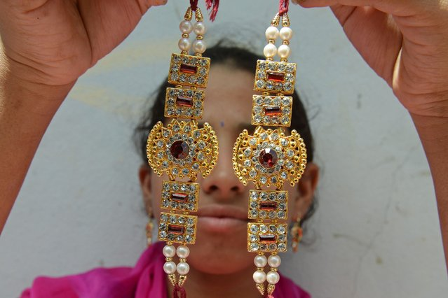 An Indian worker poses with specially designed bracelets called rakhis (sacred thread) at the Amrut rakhi workshop in Hyderabad on August 6, 2014, ahead of the Raksha Bandhan festival which falls this August 10. The Annual Raksha Bandhan festival is celebrated by sisters tying a colourful thread, or a decorative bracelet around the wrist of  her male siblings as a sign of love and affection. (Photo by Noah Seelam/AFP Photo)
