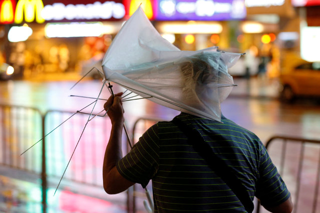 A man carrying a broken umbrella braves strong wind and rains as Typhoon Nesat hits Taipei, Taiwan July 29, 2017. (Photo by Tyrone Siu/Reuters)