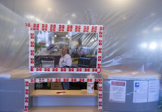 An employee sits at the cash desk area in the Handelshof behind a temporary foil wall with a window and a small opening for issuing invoices in Schwerin, Germany, Tuesday, March 24, 2020. Grocery stores are still open, and protective walls and films are to protect employees from the corona virus. Public life in Mecklenburg-Western Pomerania will be further restricted in connection with protective measures against the spread of the coronavirus. (Photo by Jens Buettner/dpa via AP Photo)
