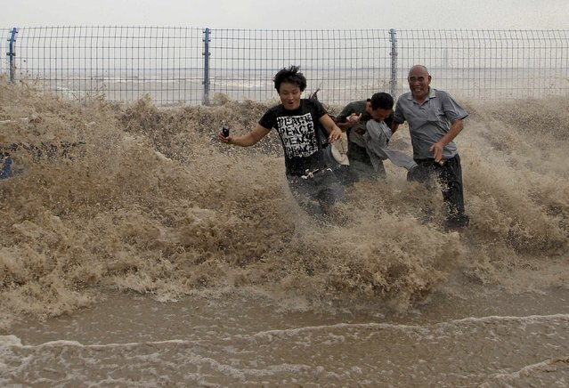 Visitors run from waves caused by a tidal bore as it surges past a barrier on the banks of Qiantang River, in Hangzhou Zhejiang province, September 21, 2013. (Photo by Reuters/Stringer)