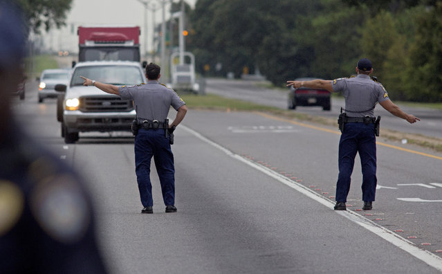 State Police block direct traffic off Airline Highway after Baton Rouge police were shot in Baton Rouge, La., on Sunday, July 17, 2016. Multiple law enforcement officers were killed and wounded Sunday morning in a shooting near a gas station in Baton Rouge, less than two weeks after a black man was shot and killed by police here, sparking nightly protests across the city. (Photo by Max Becherer/AP Photo)