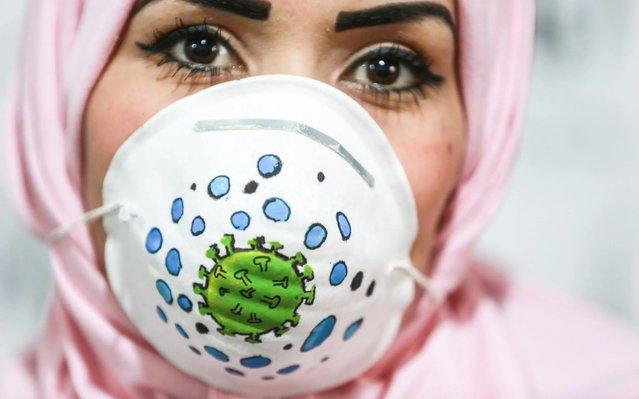Gazan artist wears a face mask to raise awareness to the novel coronavirus (Covid-19) spread in Gaza Strip on March 25, 2020. (Photo by Ali Jadallah/Anadolu Agency via Getty Images)