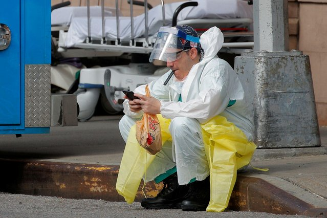 A healthcare worker sits on the curb as he uses a vaping device while taking a break outside Maimonides Medical Center during the outbreak of the coronavirus disease (COVID-19) in the Brooklyn borough of New York City, New York, U.S., April 7, 2020. (Photo by Brendan Mcdermid/Reuters)