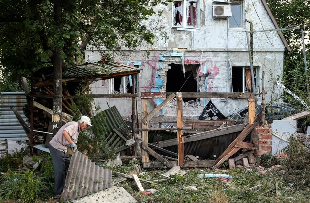 A man picks up debris damaged after Ukranian army shelling downtown of Donetsk, Ukraine, 20 August 2014. Thirty-four people have been killed in fighting between separatist militants and government troops in Ukraine's eastern Donetsk region over the past 24 hours, the local government said. Fighting was reported from the rebel-held city of Donetsk and its eastern outskirts. City authorities said that artillery battles were raging. (Photo by Sergei Ilnitsky/EPA)