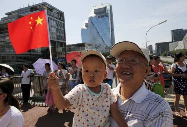 A boy holds Chinese national flag as he and his grandfather wait for the performance of military helicopters and planes during the military parade marking the 70th anniversary of the end of World War Two, in Beijing, China, September 3, 2015. (Photo by Kim Kyung-Hoon/Reuters)