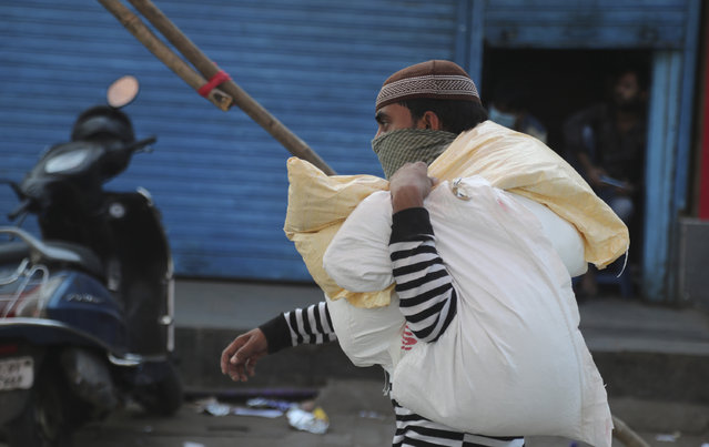 A migrant worker carries sacks of wheat and rice in Dharavi, one of Asia's largest slums, during a lockdown in Mumbai, India, Friday, April 17, 2020. Indian Prime Minister Narendra Modi on Tuesday extended the world's largest coronavirus lockdown to head off the epidemic's peak, with officials racing to make up for lost time. (Photo by Rafiq Maqbool/AP Photo)