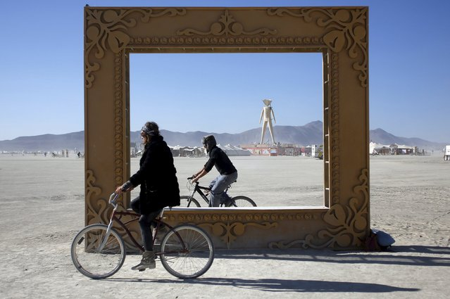 "Participants ride around the art installation ""Got Framed"" during the Burning Man ""Carnival of Mirrors"" arts and music festival in the Black Rock Desert of Nevada, September 4, 2015. (Photo by Jim Urquhart/Reuters)"
