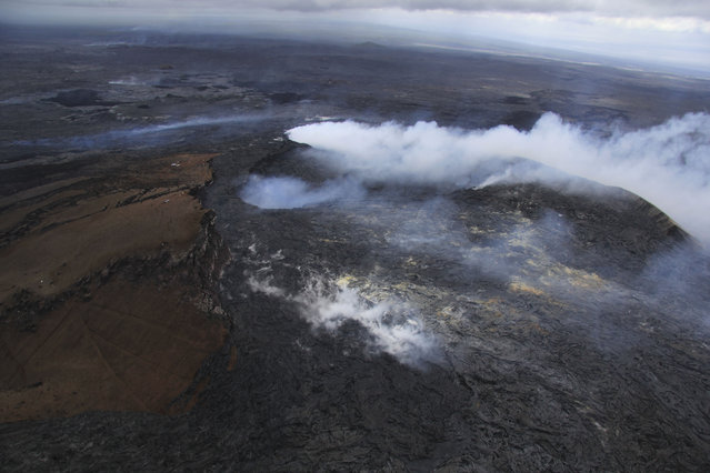 This August 22, 2014 photo released by the U.S. Geological Survey shows the Pu'u 'O'o crater of the Kilauea volcano partially obscured by thick fume from the June 27 lava flow near Pahoa, Hawaii. (Photo by Tim Orr/AP Photo/U.S. Geological Survey)