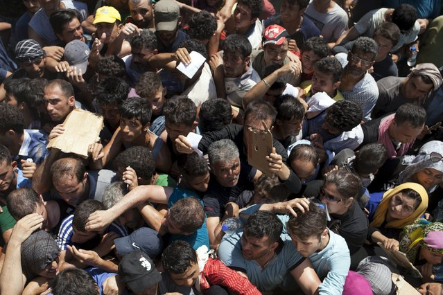 Refugees and migrants are packed together while waiting for a registration procedure at the port of Mytilene on the Greek island of Lesbos, September 5, 2015. (Photo by Dimitris Michalakis/Reuters)