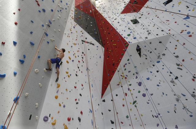 """A man climbes a vertical wall at the """"Bleau"""" indoor climbing gym, in Ghent, western Belgium, Monday, September 8, 2014. With more than 3,500 square meters (37,673 square feet) of climbing surface, the new gym is one of the five largest climbing structures in the world. (Photo by Yves Logghe/AP Photo)"""