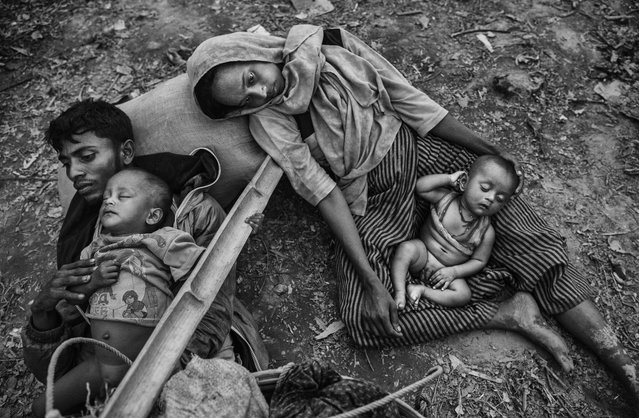 A Rohingya refugee family rest as they sit on the ground on the Bangladesh side of the Naf River after fleeing Myanmar, on October 2, 2017 in Cox's Bazar, Bangladesh. (Photo by Kevin Frayer/Getty Images)