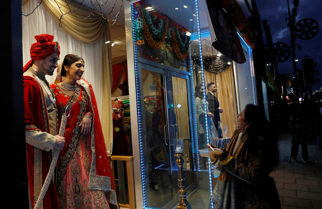 A woman laughs as she looks at a window display using real life models in a shop window during the Diwali lights switch on in Leicester, Britain October 8, 2017. (Photo by Darren Staples/Reuters)