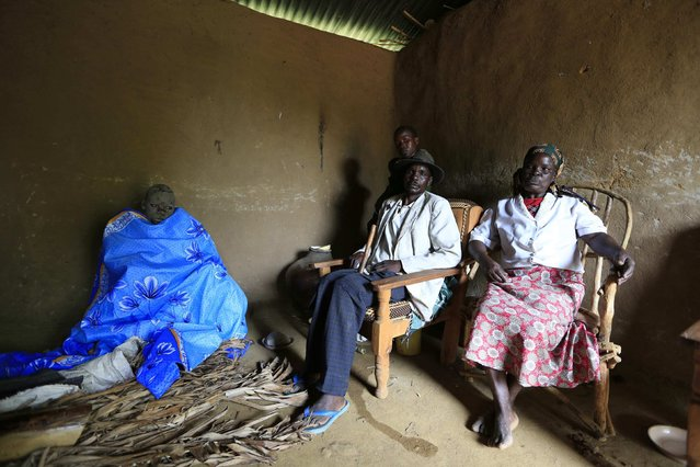 A Bukusu family sits next to their son who just underwent circumcision inside a house in Kenya's western region of Bungoma August 8, 2014. (Photo by Noor Khamis/Reuters)