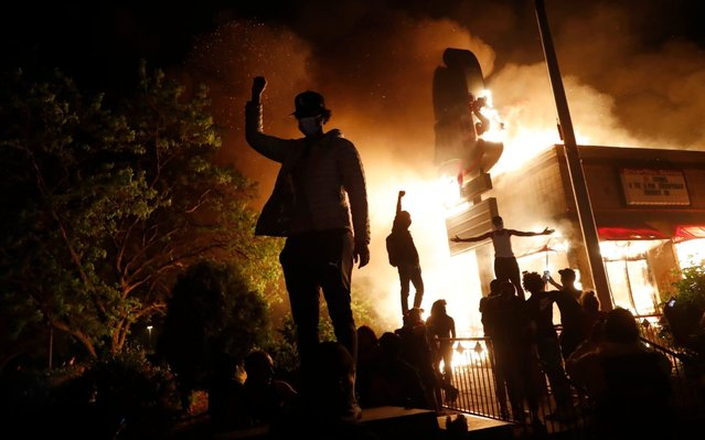Protestors demonstrate outside of a burning fast food restaurant, Friday, May 29, 2020, in Minneapolis. Protests over the death of George Floyd, a black man who died in police custody Monday, broke out in Minneapolis for a third straight night. (Photo by John Minchillo/AP Photo)