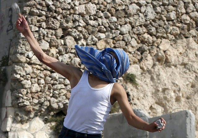 A Palestinian youth throws a stone towards Israeli police during clashes in the east Jerusalem neighbourhood of Issawiya September 13, 2015, after Israeli police raided the plaza outside Jerusalem's al-Aqsa mosque on Sunday, in what they said was a bid to prevent Palestinian attempts to disrupt visits by Jews and foreign tourists on the eve of the Jewish New Year. (Photo by Ammar Awad/Reuters)