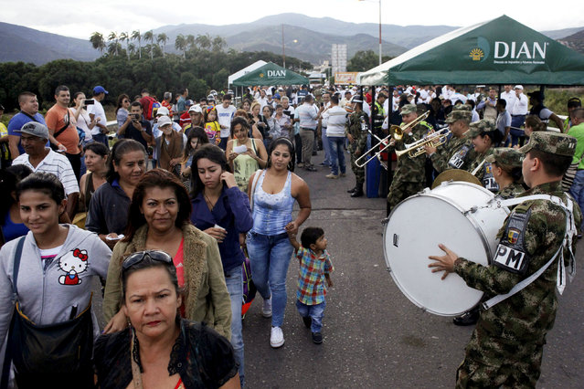 People walk next to Colombian soldiers while they cross to Colombia over the Simon Bolivar international bridge in Cucuta, Colombia, August 13, 2016. (Photo by Carlos Eduardo Ramirez/Reuters)