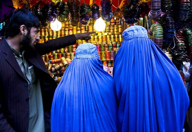 Women shop at a market ahead of the upcoming Eid al-Adha, or the Feast of the Sacrifice in Jalalabad east of Kabul, Afghanistan October 24, 2012. (Photo by Rahmat Gul/Associated Press)