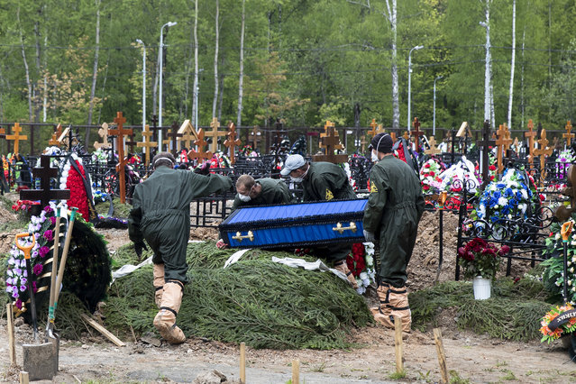 In this May 26, 2020, file photo, grave diggers wearing protective suits carry a coffin of a COVID-19 victim for burial in the section of a cemetery reserved for coronavirus victims, outside Moscow, Russia. The way Russia counts fatalities during the coronavirus pandemic could be one reason why its official death toll is far below many other countries, even as it has reported at least 511,000 infections, behind only the United States and Brazil. (Photo by Pavel Golovkin/AP Photo/File)