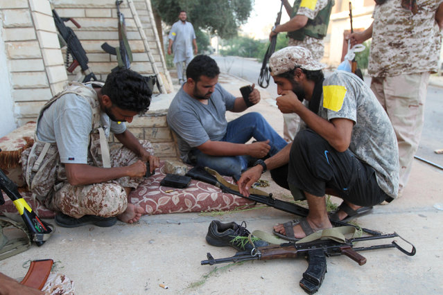 Fighters from Libyan forces allied with the U.N.-backed government load their weapon magazines during a battle with Islamic State fighters in Sirte, Libya August 21, 2016. (Photo by Hani Amara/Reuters)