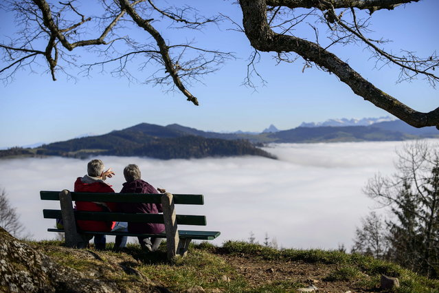 An elderly couple sit on a bench above fog hanging in the valley of Hochwacht mountain above Zug, central Switzerland on November 20, 2012. (Photo by Fabrice Coffrini/AFP Photo)