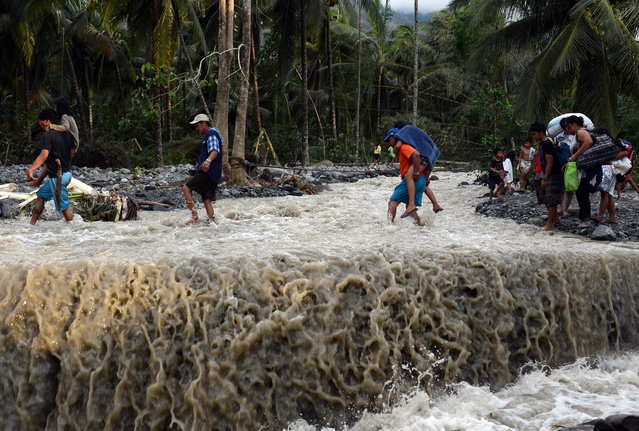 Residents cross a damaged road destroyed at the height of Typhoon Bopha in the village of Andap, New Bataan town, Compostela Valley province, on December 5, 2012. (Photo by Ted Aljibe)