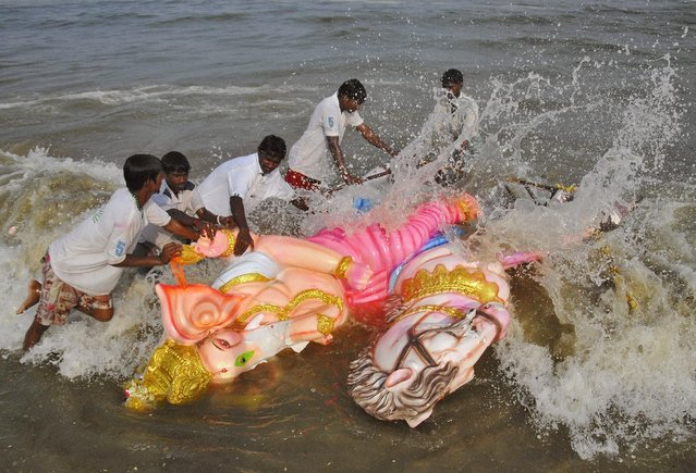 Volunteers immerse an idol of the Hindu god Ganesh, the deity of prosperity, into the Bay of Bengal on the last day of the ten-day-long Ganesh Chaturthi festival in Chennai, India, September 27, 2015. (Photo by Reuters/Stringer)