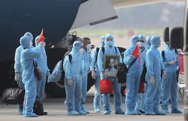Vietnamese COVID-19 patients in protective gear, holding Vietnamese flags and carrying a portrait of the national leader Ho Chi Minh, arrive at the Noi Bai airport in Hanoi, Vietnam, on Wednesday, July 29, 2020. The 129 patients who were working in Equatorial Guinea are brought home in a repatriation flight for treatment of the coronavirus. (Photo by Tran Huy Hung/VNA via AP Photo)