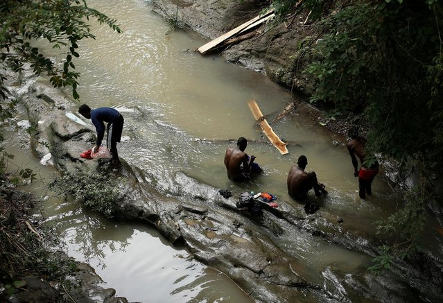 Africans migrants stranded in Costa Rica wash their clothes in a river at the border between Costa Rica and Nicaragua, in Penas Blancas, Costa Rica, September 7, 2016. (Photo by Juan Carlos Ulate/Reuters)
