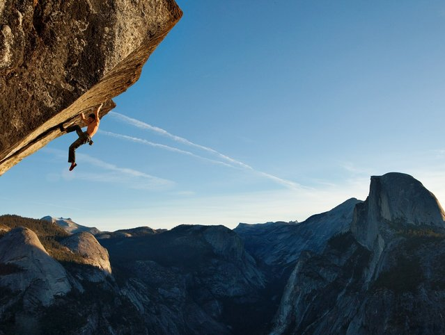 """Climbing without a rope in Yosemite National Park, Dean Potter scales a route called """"Heaven."""" (Photo by Mike Schaefer"""