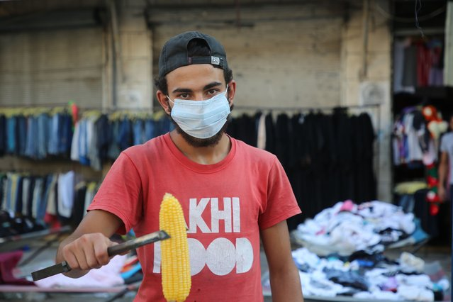 A Syrian youth sells corn on a main street in Idlib wearing a protective mask as a preventive measure to prevent infection with the Coronavirus, as the first case of the virus was recorded the day before, on July 10, 2020. (Photo by Muhammad al-Rifai/NurPhoto via Getty Images)