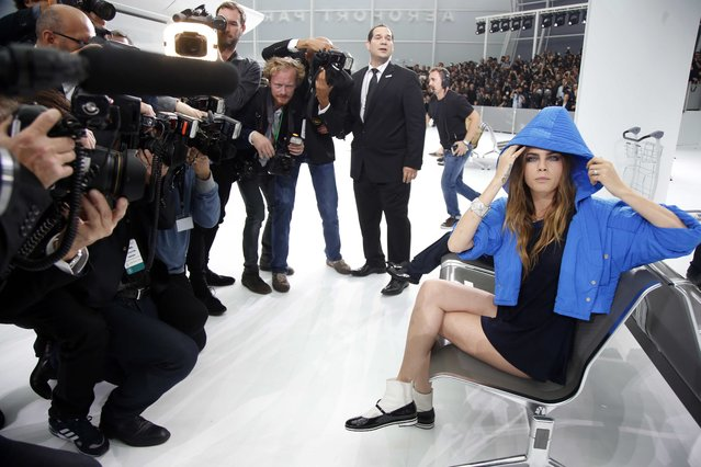 Model Cara Delevingne is surrounded by photographers as she arrives to attend German designer Karl Lagerfeld's Spring/Summer 2016 women's ready-to-wear collection show for fashion house Chanel at the Grand Palais which is transformed into a Chanel airport during the Fashion Week in Paris, France, October 6, 2015. (Photo by Charles Platiau/Reuters)