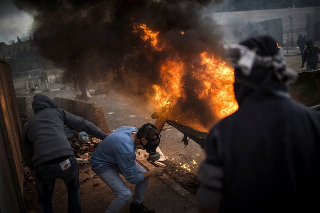 Palestinian youth clash with police at Shuafat refugee camp after a Palestinian resident of the camp was named as the driver of a van that rammed into a crowd at a rail stop on November 5, 2014 in Jerusalem, Israel. Clashes started at the refugee camp following the attack in which one person was killed and at least 13 people were wounded after a driver crashed into pedestrians during a suspected terror attack near East Jerusalem. (Photo by Ilia Yefimovich/Getty Images)