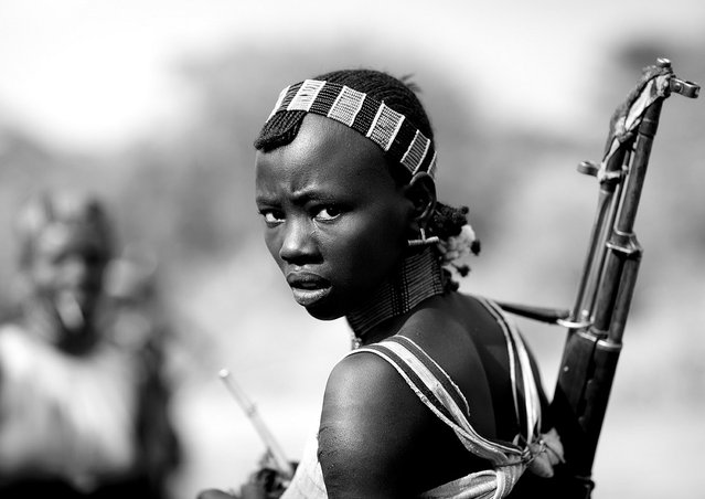 """Hamer girl with gun – Omo Ethiopia. During bull jumping ceremony, Hamer girls act like men, and even more, to show that they do not fear anything. So they drink a lot, and they dance with guns. Very impressive ceremony!